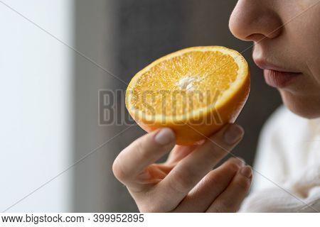 Sick Woman Trying To Sense Smell Of Half Fresh Orange, Has Symptoms Of Covid-19, Corona Virus Infect