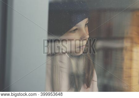 A Sad Girl In A Black Cap Looks Out The Window.