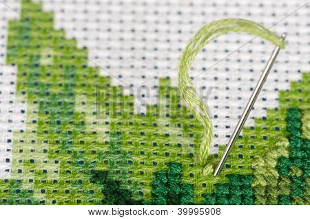 Cross stitching with a needle closeup
