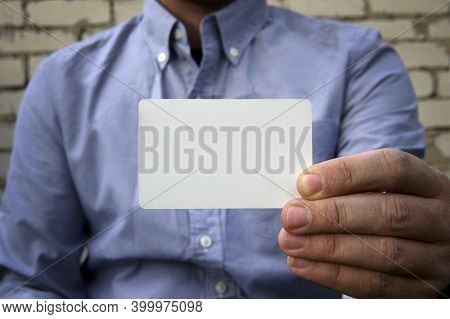 Business Man Handing A Blank Business Card Over Background White Brick Wall On The Street. A Plastic