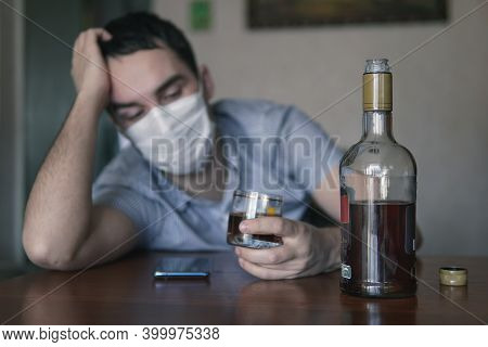 Man With Alcohol Wearing Medical Mask. Drunkenness In Conditions Of Self-isolation And Quarantine. T
