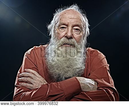 Old age concept. Portrait of an old man with white beard sadly looking at camera. Black background.
