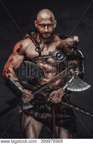 Savage And Skilled Scandinavian Warrior With Bald Head Wielding Two Axes And In Armour With Fur In D