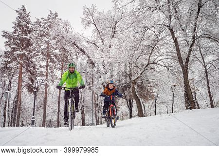 Father And Son Ride Bicycles In The Winter Park. Bearded Man And Boy On Bicycles Spend Family Weeken