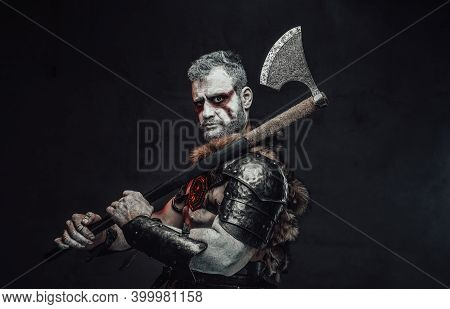 Fantasy Barbaric Soldier Armed With Huge Axe In Dark Armour With Fur Poses In Dark Background Holdin