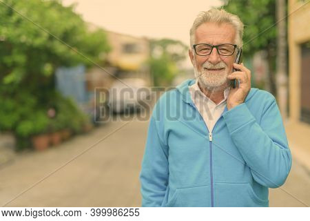 Happy Handsome Senior Bearded Man Smiling While Talking On Mobile Phone And Wearing Eyeglasses Outdo