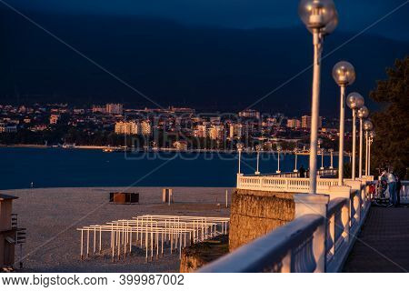 Embankment With Balustrade At Sunset. View Of The Beach, Bay And Mountains. The Balustrade Is Beauti