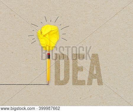 Yellow Paper Light Bulb Metaphor For Creative And New Idea With Pencil On Brown Recycled Background
