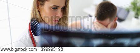 Woman Doctor With Sad Face Holds An X-ray From Behind On Background The Patient Sits With His Head D
