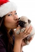 female wearing Christmas hat and kissing puppy against white background poster