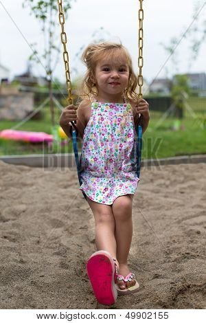 Little Girl Swinging After A Meal