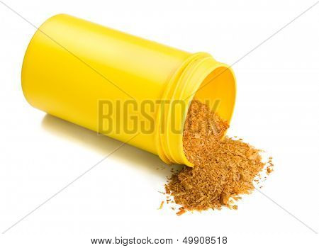 Dried aquarium fish feed in yellow plastic container isolated on white