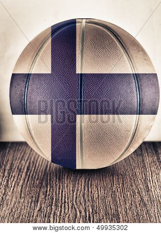 Close up of an old leather basketball with Finland flag poster