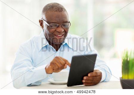 fröhlich senior afroamerikanischer Mann mit Tablettcomputer zu Hause