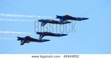 Four Navy FA-18 Blue Angels jets flying upside down in a precision pattern
