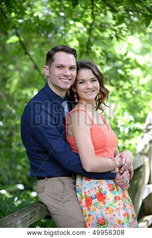 Young happy couple posing on a bridge after their engagement in a garden setting