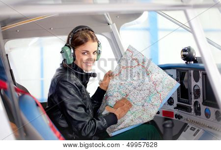 Portrait of young beautiful woman pilot in a airplane.