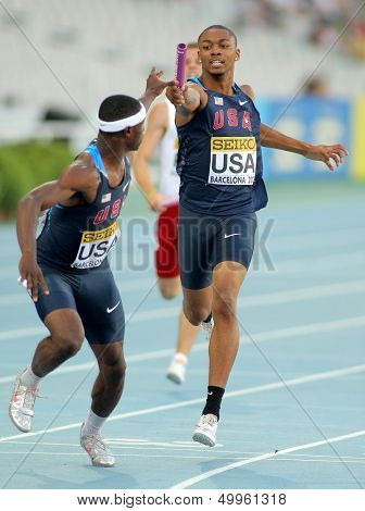 BARCELONA - JULY, 14: Eric Futch(L) and Quincy Downing(R) of USA competes on 4X400 Relay of the 20th World Junior Athletics Championships at the Stadium on July 14, 2012 in Barcelona, Spain