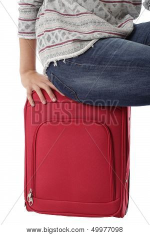 Woman Sitting on a Red Suitcase