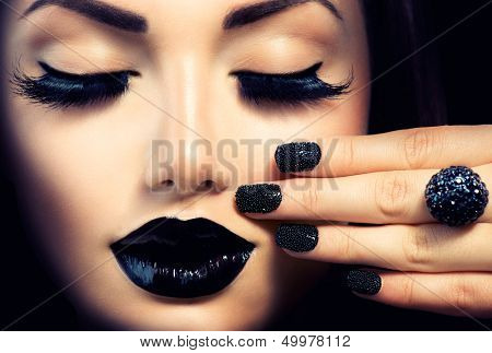 Beauty Fashion Model Girl with Black Make up, Long Lushes. Fashion Trendy Caviar Black Manicure. Nail Art. Dark Lipstick and Nail Polish. Isolated over black background poster