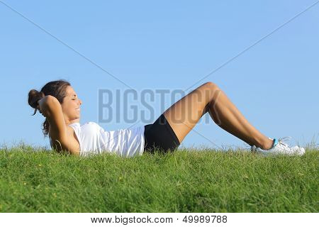 Beautiful Woman Doing Crunches On The Grass With The Sky In The Background