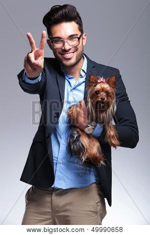 casual young man holding a puppy and showing the victory sign while smiling for the camera. on gray background poster
