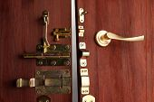 Metal bolts, latches and hooks in wooden open door close-up poster
