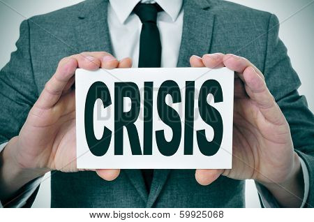 a man wearing a signboard with the word crisis written in it