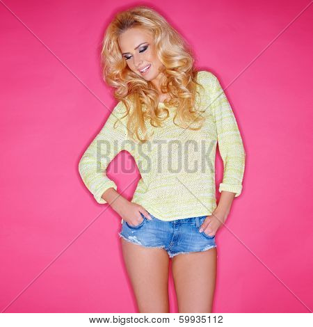 Glamorous blond woman with her long hair in ringlets in trendy skimpy denim shorts posing confidently with her hands in her pockets and a jaunty attitude