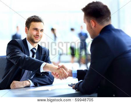 Two business colleagues shaking hands during meeting poster