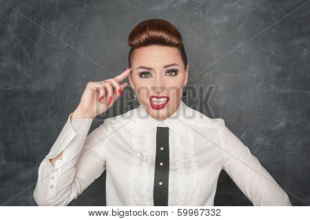 Beautiful young fashion woman gesturing with finger to her head poster