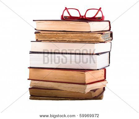 A pile of old books isolated on white background. Glasses in the red-rimmed from above.