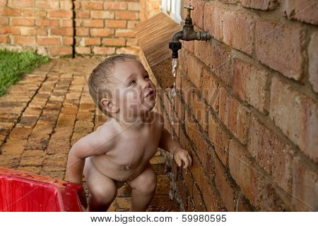 Baby boy drinking water from a tap
