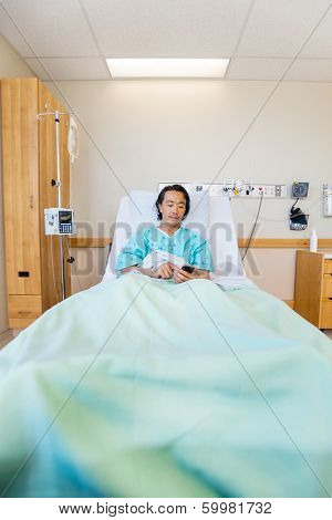 Full length of mature male patient messaging through mobile phone on bed in hospital