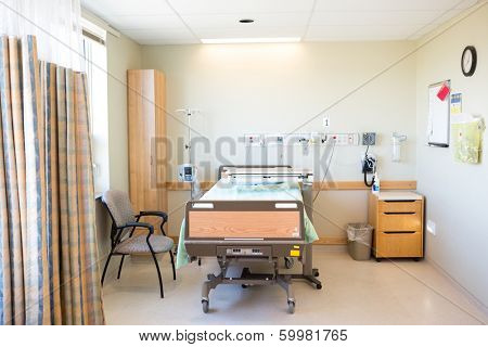 Interior of hospital room with bed and chair