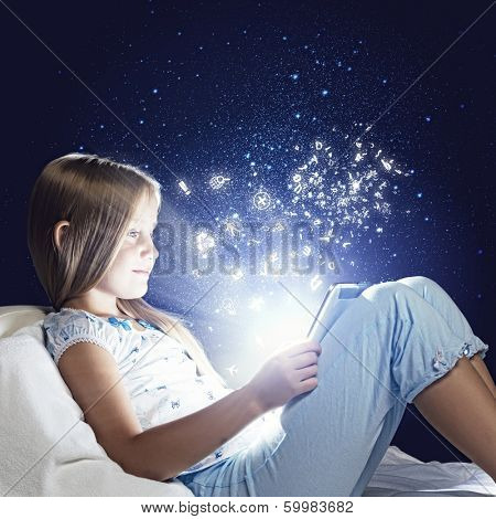 Girl sitting in bed and using tablet pc