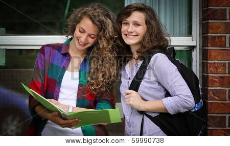 Two smiling students with their bags at school studying