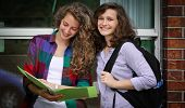 Two smiling students with their bags at school studying poster