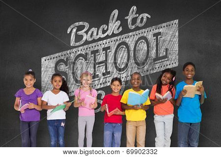 Elementary pupils reading books against black wall with back to school message poster