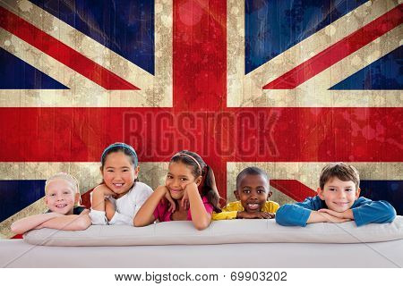 Cute pupils smiling at camera against union jack flag in grunge effect poster