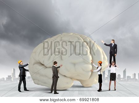 Huge human brain and many little businesspeople around