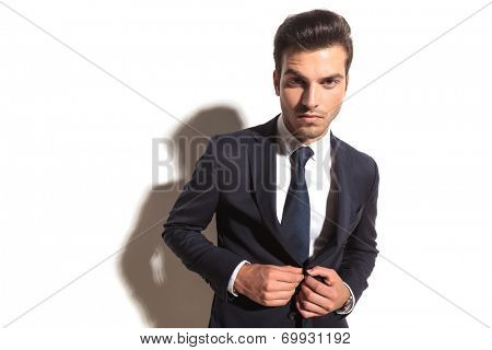 dramatic fashion business man un bottoning his coat on white studio background