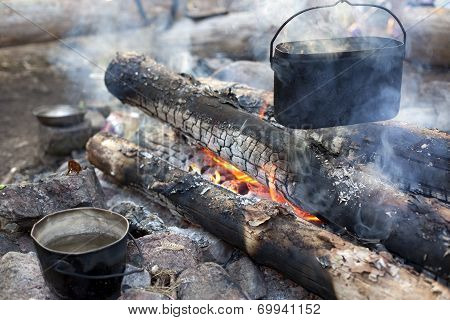 A Dixy On The Fire Is On Stones In The Forest