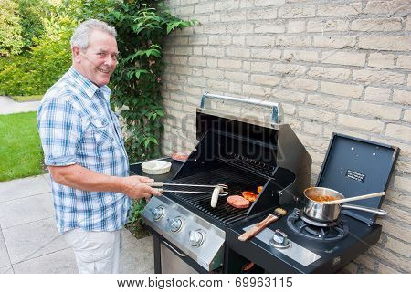 Retired Dutch Senior Man Grilling Meat