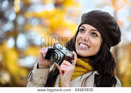 Woman Taking Photo With Retro Camera In Autumn
