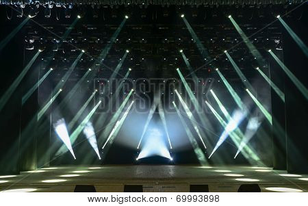 Illuminated empty concert stage with smoke and rays of light poster
