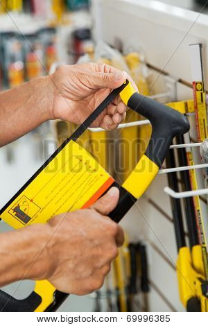 Midsection of senior salesman examining hacksaw in hardware store poster