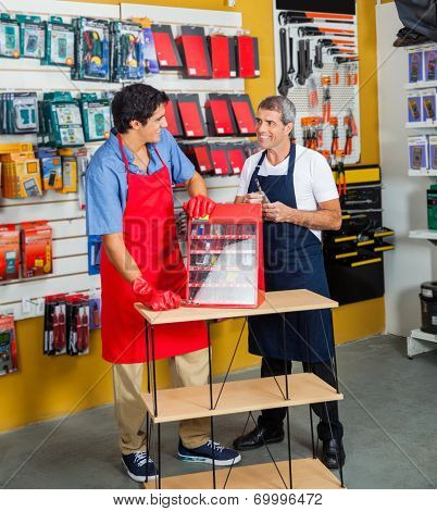 Full length of salesmen with drill toolbox looking at each other in hardware store
