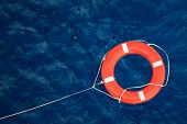 Lifebuoy in a stormy blue sea, safety equipment in boat poster