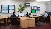 Technicians sitting in office running diagnostics in large data center poster